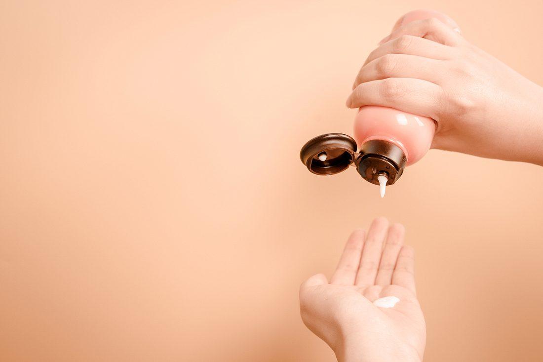 AHA-Peeling tropft auf eine Frauenhand
