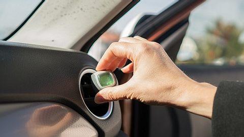 Frau installiert Autoduft im Auto - Foto: iStock/mustafagull
