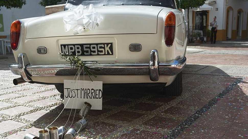Autoschmuck für Hochzeiten an weißem Auto - Foto: iStock/Maria Teijeiro
