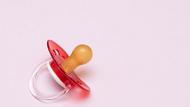 Baby Schnuller auf rosa Hintergrund - Foto: iStock/DevMarya