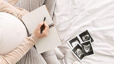 Schwangere Frau gestaltet Babybuch - Foto: iStock/Prostock-Studio