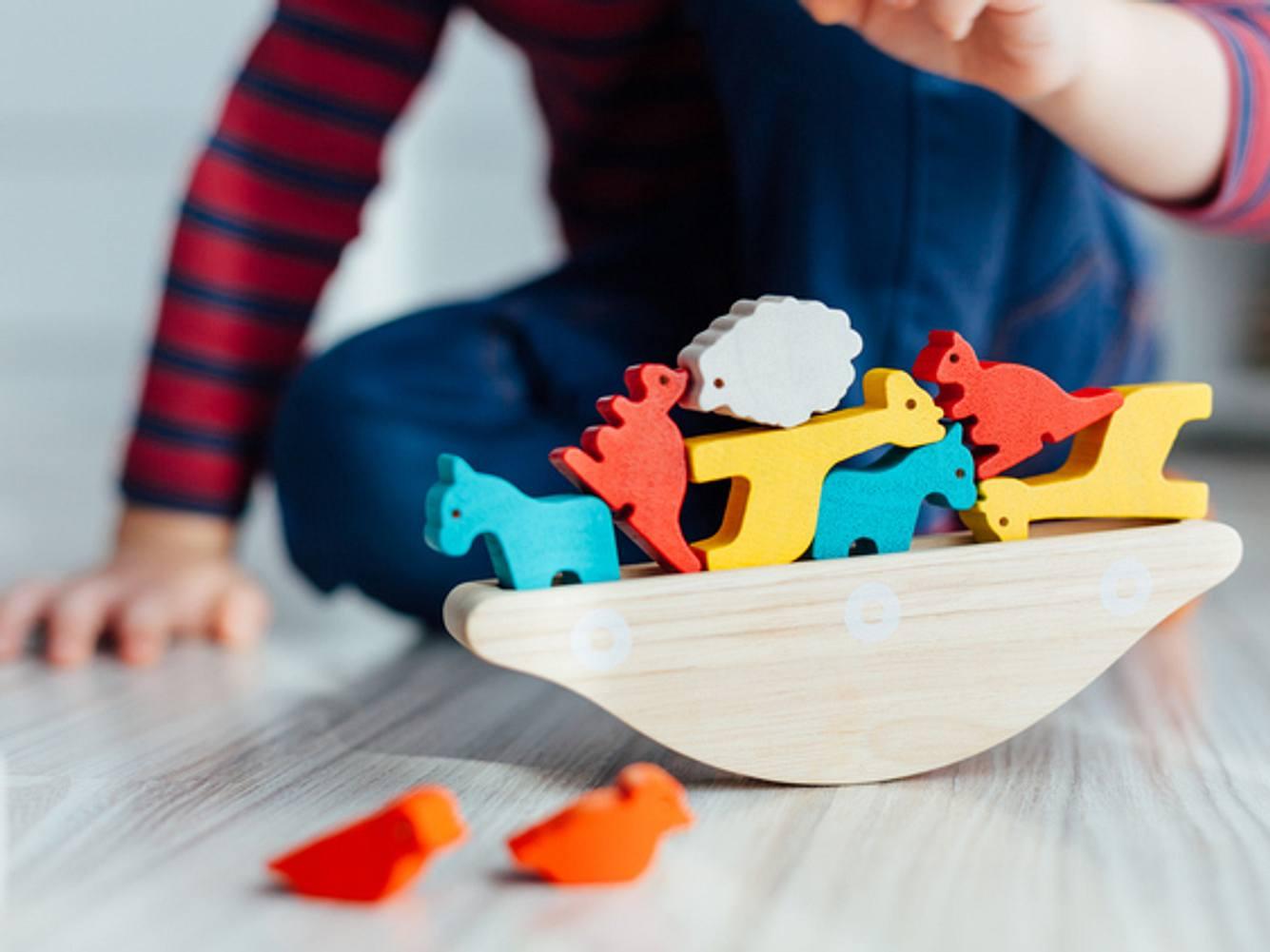 Kind spielt mit Bauernhof-Tieren aus Holz