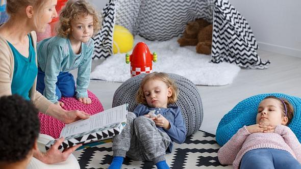 Frau liest Vorschulkindern ein Buch vor - Foto: iStock/KatarzynaBialasiewicz