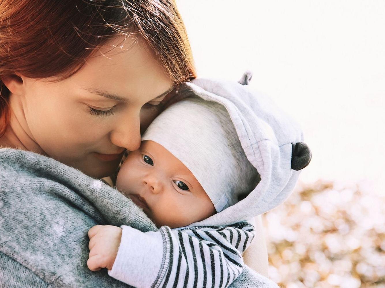 Mama mit Baby auf dem Arm, das mit Mütze und warmen Jäckchen abgebildet ist