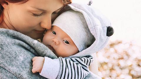 Mama mit Baby auf dem Arm, das mit Mütze und warmen Jäckchen abgebildet ist - Foto: iStock/NataliaDeriabina