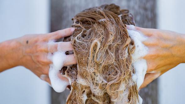 Frau wäscht sich die Haare mit Bio-Shampoo. - Foto: iStock/ StockPlanets