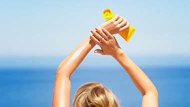 Frau cremt sich mit Bio-Sonnencreme ein. - Foto: iStock/ Tom Merton
