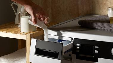 Mensch füllt Bio-Waschmittel in Vorrichtung an der Waschmaschine. - Foto: iStock/JazzIRT
