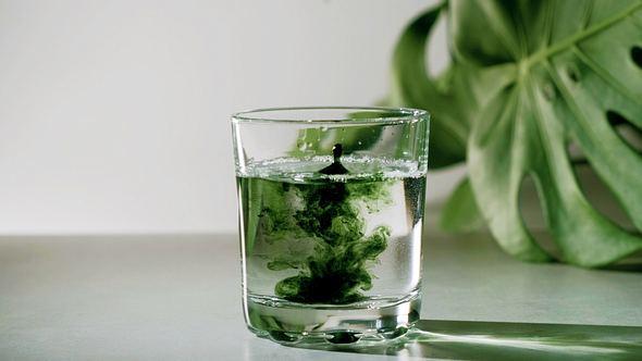 Glas mit Wasser und Chlorophyll-Tropfen - Foto: iStock/AVRORRA