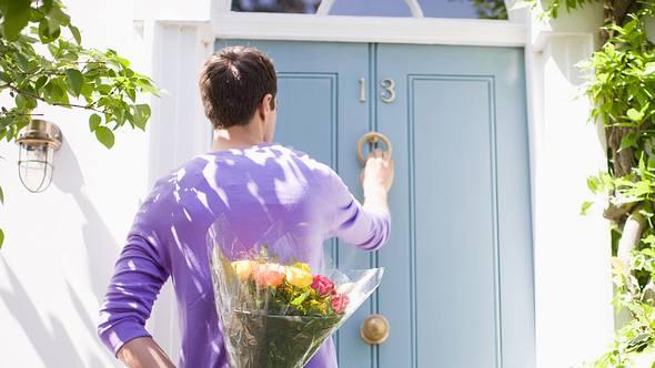 Mann steht vor einer Tür mit einem Blumenstrauß hinter seinem Rücken - Foto: Robert Daly / iStock