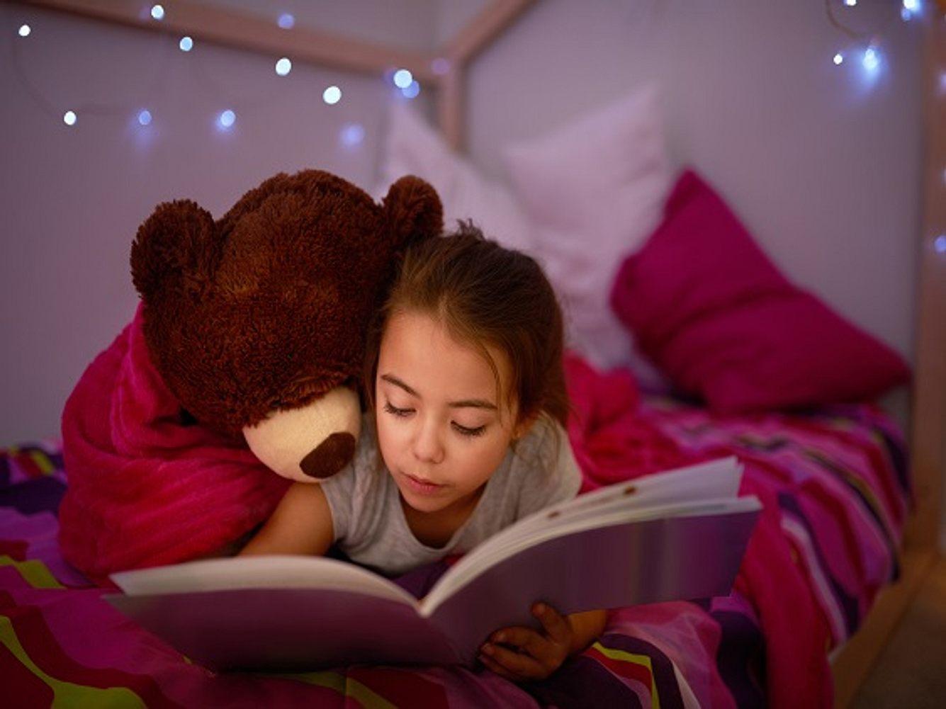 Braunhaariges Mädchen liegt lesend auf Bett