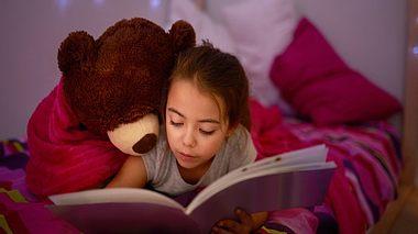 Braunhaariges Mädchen liegt lesend auf Bett - Foto: iStock/PeopleImages