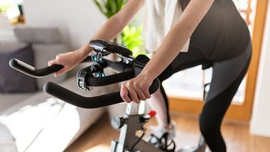 Frau trainiert auf einem Fahrradtrainer - Foto: iStock/SimonSkafar