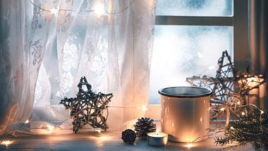 weihnachtlich dekoriertes Fenster mit Lichterkette - Foto: iStock/sofiaworld