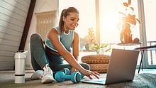 Frau sportelt mit Fitness-Produkten zu Hause - Foto: iStock