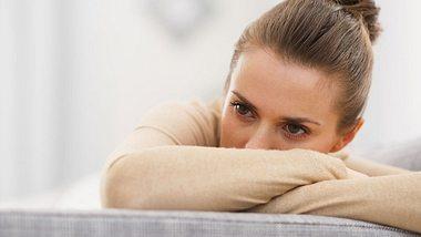 Junge Frau schaut nachdenklich und stützt ihren Kopf auf die verschränkten Arme. - Foto: CentralITAlliance / iStock
