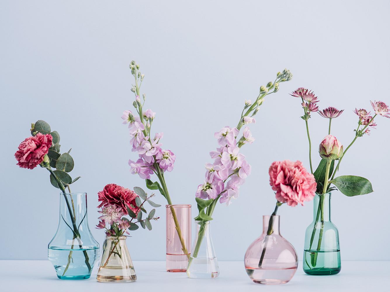 Glasvasen mit Blumen dekorieren