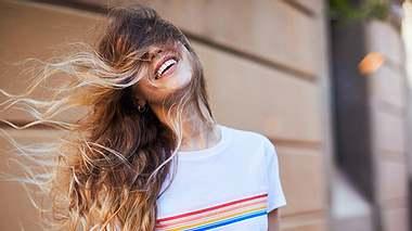 Frau freut sich über mehr Volumen ihrer Mähne dank Haarpuder - Foto: iStock/Tempura