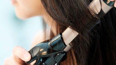 Hollywood Curls: So drehst du die Haarsträhne auf den Lockenstab. - Foto: iStock