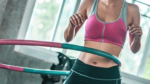 Frau im Fitnessstudio mit Hula Hoop Reifen - Foto: iStock/junce