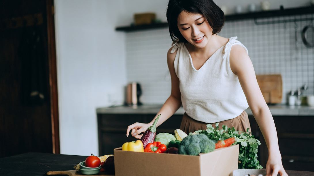 Beautiful smiling young Asian woman received a full box of colourful and fresh organic groceries ordered online by home doorstep delivery service. She is sorting out the groceries and preparing to cook a healthy meal - Foto: Getty Images