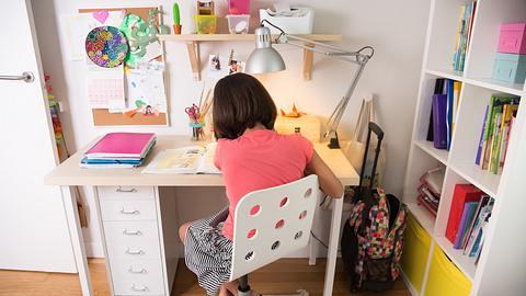 Mädchen sitzt an einem Schreibtisch für Kinder - Foto: iStock/ASIFE