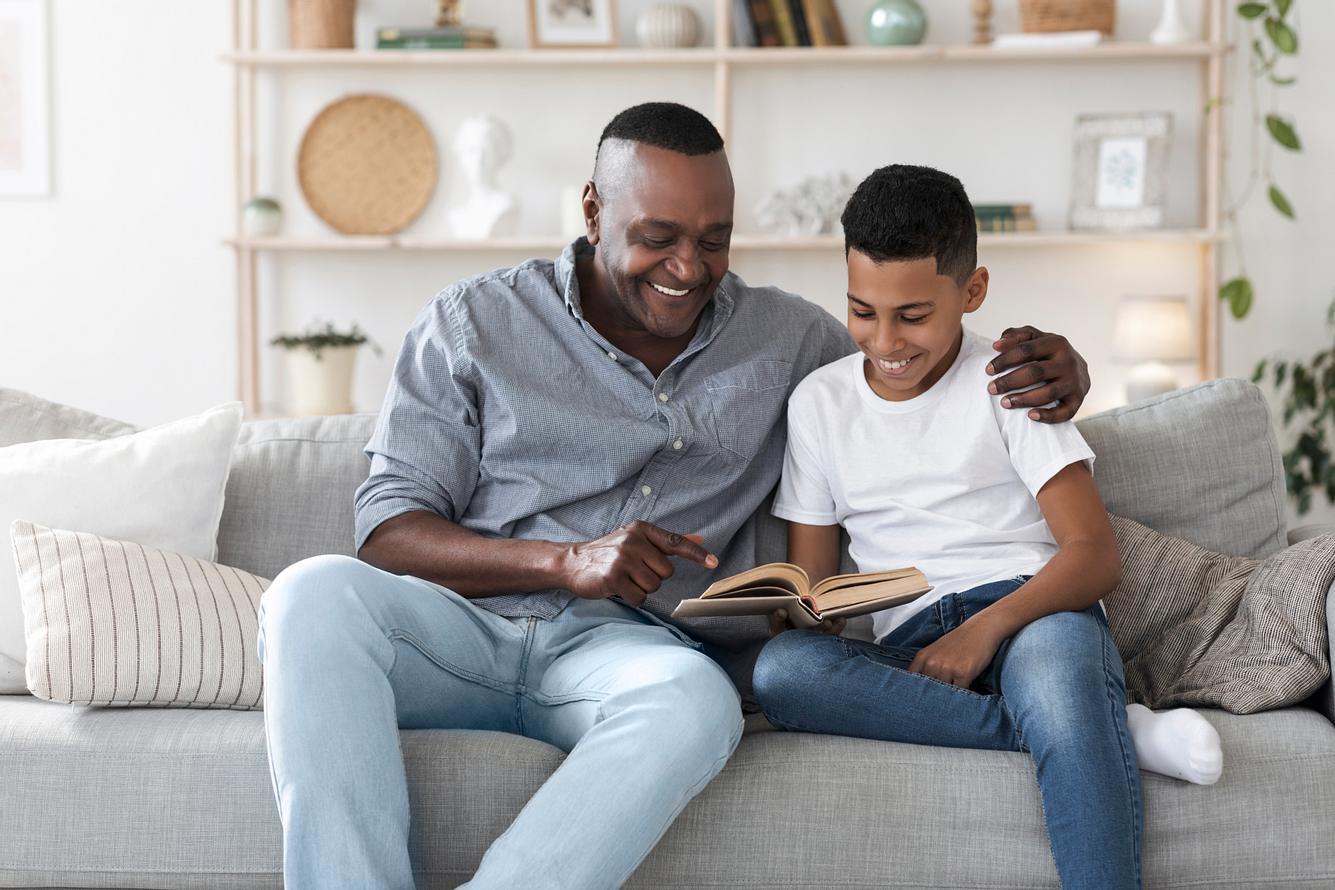 Ein Vater sitzt gemeinsam mit seinem Sohn auf einem Sofa und sie lesen gemeinsam ein Buch