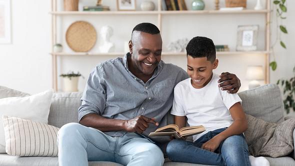 Ein Vater sitzt gemeinsam mit seinem Sohn auf einem Sofa und sie lesen gemeinsam ein Buch - Foto: iStock/Prostock-Studio
