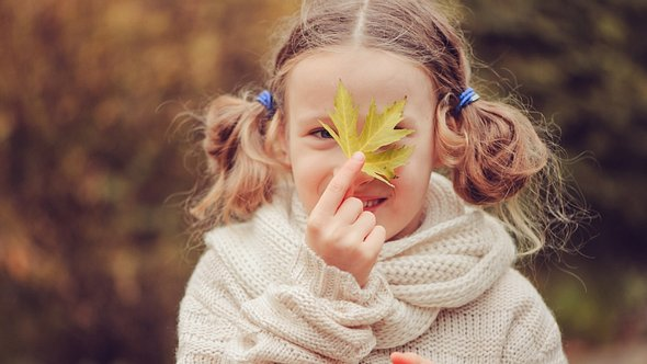 Kind hält sich ein Blatt vors Gesicht - Foto: Mkovalevskaya/iStock