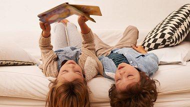 Kinder lesen Kinderbuch Klassiker auf Sofa - Foto: iStock/PeopleImages