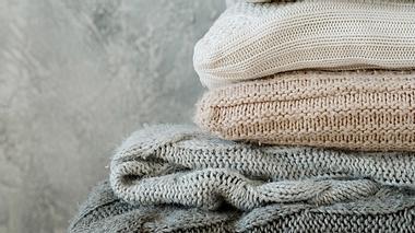 Gefaltete Kuscheldecken in verschiedenen Grau- und Beigetönen. - Foto: iStock/golubovy