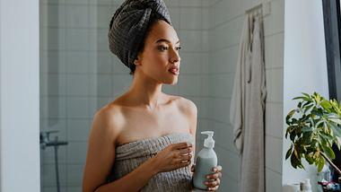 Frau hat Leave-in-Conditioner in der Hand - Foto: iStock/FreshSplash