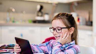 Schulmädchen sitzt für Lerncomputer und macht ihre Hausaufgaben - Foto: iStock/hedgehog94