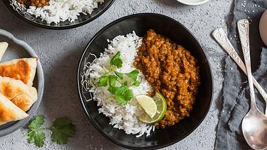 Zu Linsencurry kann Reis gereicht werden. - Foto: iStock/OksanaKiian