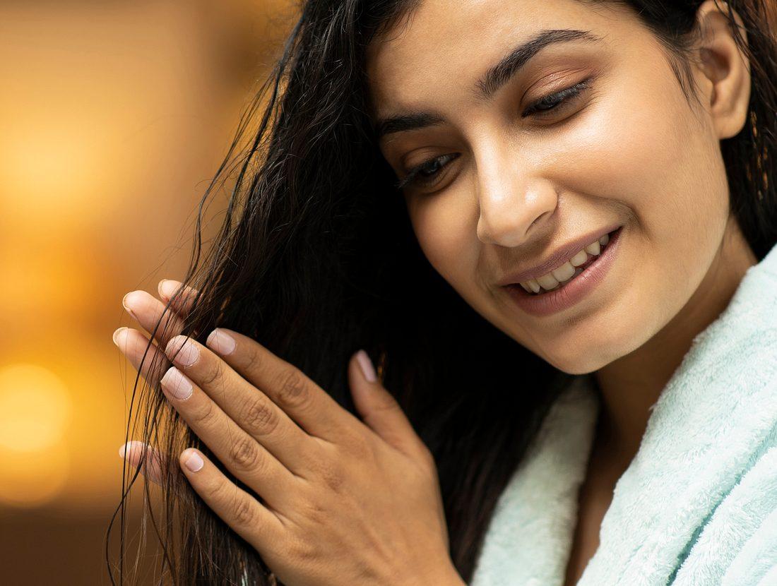 Frau reibt sich Mandelöl in ihre Haare