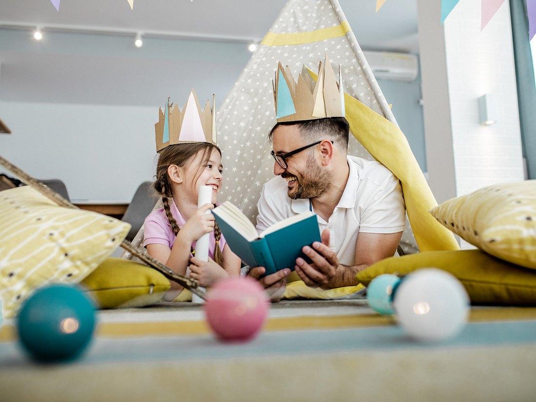 Vater und Tochter lesen Märchenbücher in Spielzelt