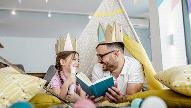 Vater und Tochter lesen Märchenbücher in Spielzelt - Foto: iStock/blackCAT