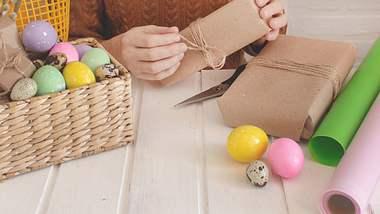 Frau packt Ostergeschenke ein. - Foto: iStock/ Olesia Oreshkina