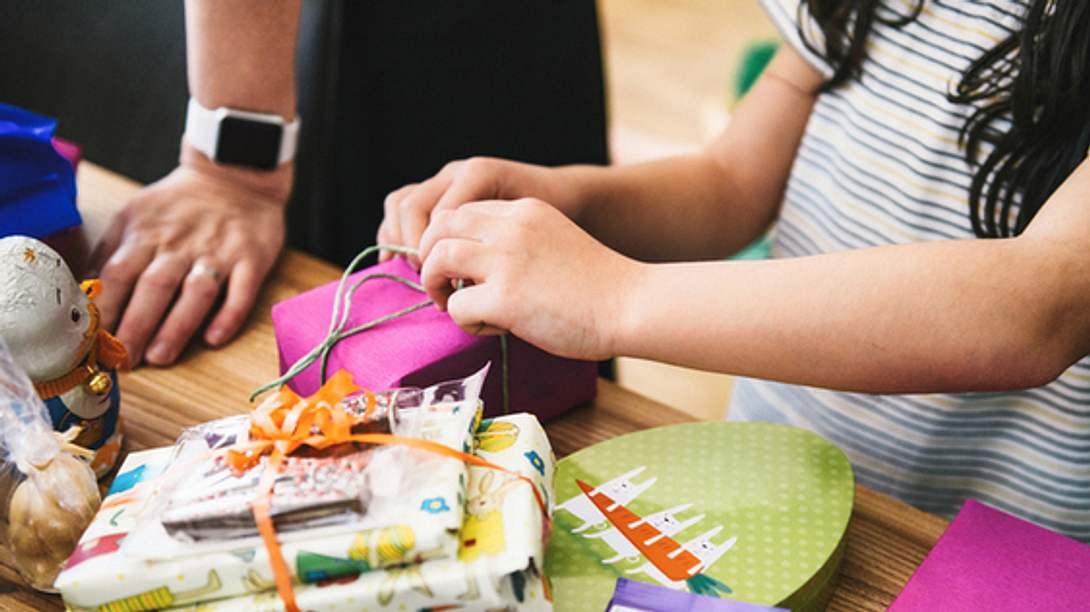 Kind öffnet personalisierte Geschenke für Kinder - Foto: iStock/golero