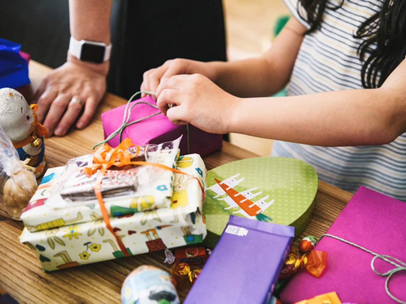 Kind öffnet personalisierte Geschenke für Kinder