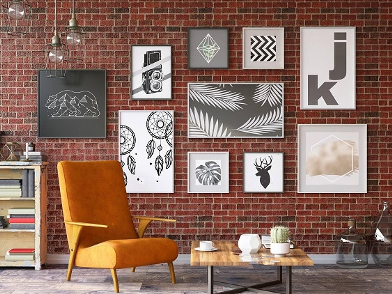 Verschiedene Poster mit Rahmen vor Backsteinwand