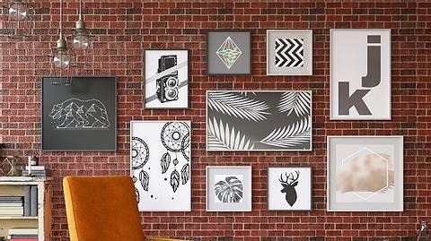 Verschiedene Poster mit Rahmen vor Backsteinwand - Foto: iStock/ asbe