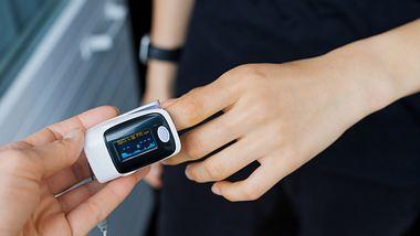 Eine Person misst ihre Werte mit einem Pulsoximeter - Foto: iStock/Ekaterina Rekina
