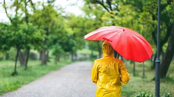 Frau mit wasserdichtem Regenmantel und Regenschirm - Foto: iStock/urbazon