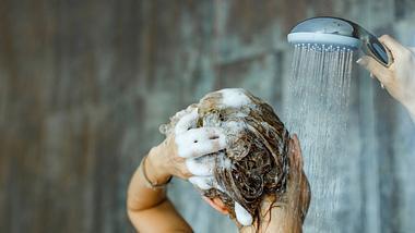 Frau wäscht Haar mit Reinigungsshampoo - Foto: skynesher / iStock
