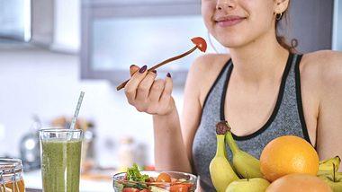 Junge Frau in Sportkleidung isst einen Salat. - Foto: Rasulovs / iStock