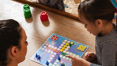 Mutter spielt mit kleiner Tochter zusammen ein Brettspiel für Kinder - Foto: iStock/StockPlanets