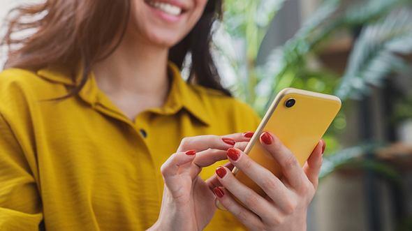 Frau hält Smartphone in der Hand. - Foto: Inside Creative House/iStock
