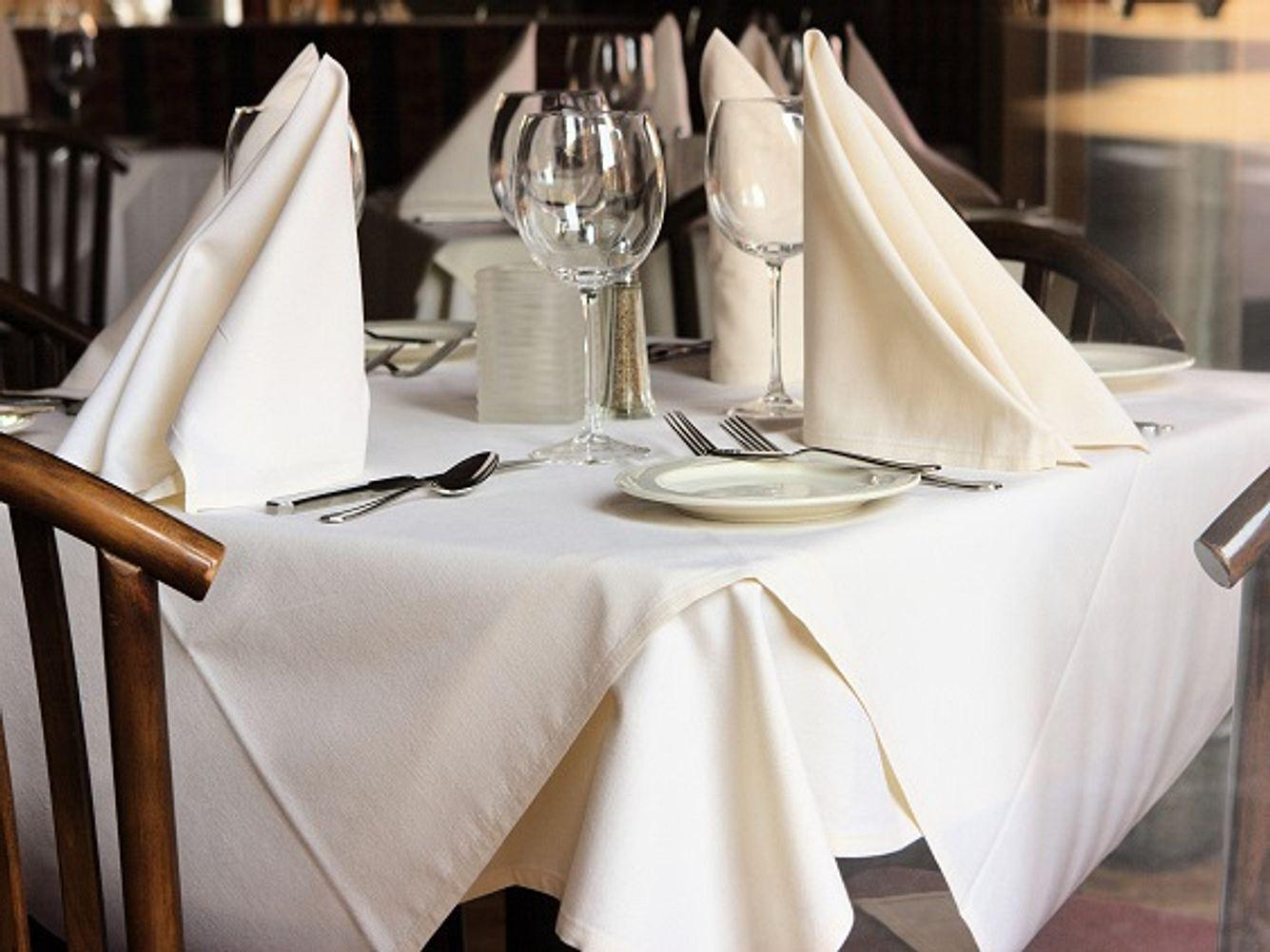 Gedeckter Tisch mit weißer Tischdecke und cremefarbenen Servietten
