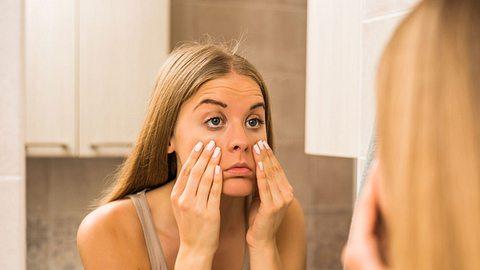 Frau betrachtet ihre Augen im Spiegel, ob sie Tränensäcke hat - Foto: LittleBee80 / iStock